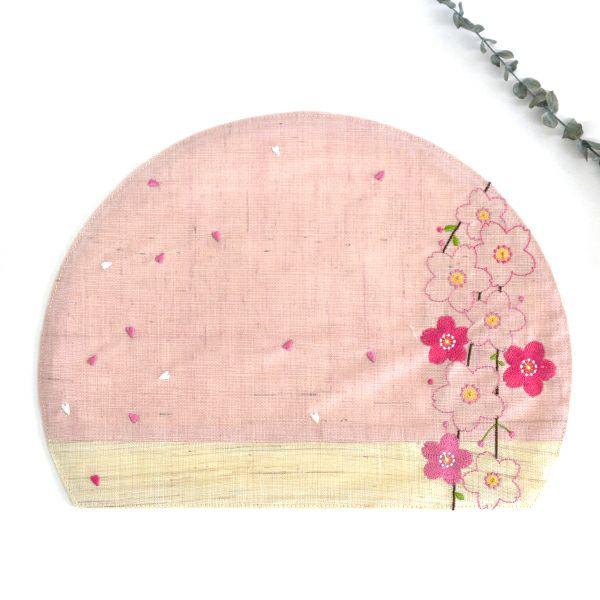 ほどよい厚みのしっかりとした生地感で、ピンク色と赤色の糸で桜の花が刺繍されたかわいいしだれ桜半月ランチョン ピンク